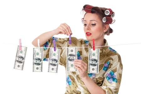 Young housewife is hanging hundred dollar bills on clothesline on a white background.  Money concept. photo