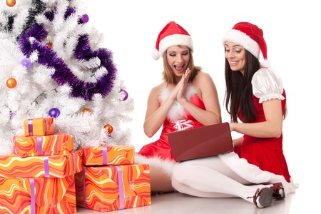 Two girlfriends with laptop and gifts sit near Christmas tree on a white background. Stock Photo - 8546974