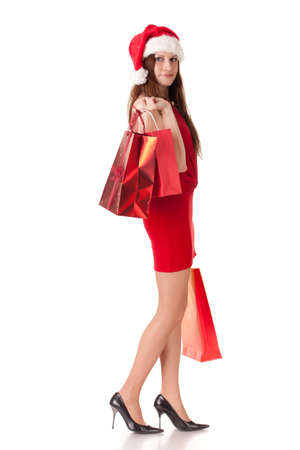 Pretty young woman in Santa's suit with shopping bags on a white background. Stock Photo - 8546964
