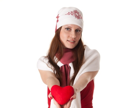 The beautiful young woman holds in hands a red heart on a white background. Selective focus on heart. photo