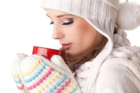 warm clothes: Giovane donna bella calda abiti invernali con tazza rossa su sfondo bianco.