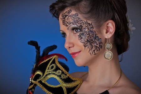 Portrait of a young beautiful woman with mask on a blue background. photo