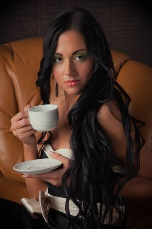 Attractive young woman lying on a leather sofa with cup of coffee. photo