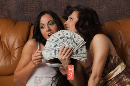 Young happy women with money sit on leather sofa at home. Shopping. Stock Photo - 8672812