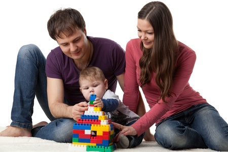 Happy family with sweet baby build house on a white background.  Concept of  building and purchase  of the house.