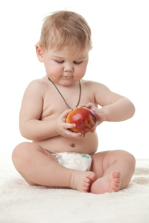 Sweet small baby with a fresh red apple on a white background. Stock Photo - 8672782