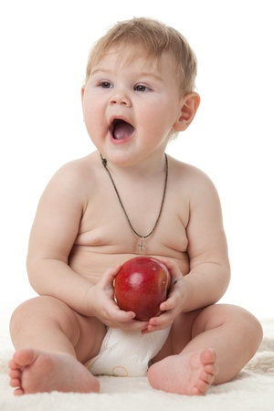 Sweet small baby with a fresh red apple on a white background. Stock Photo - 8672759
