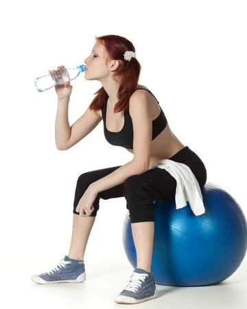 Young  beautiful woman with bottle of water and gymnastic ball on a white background. photo