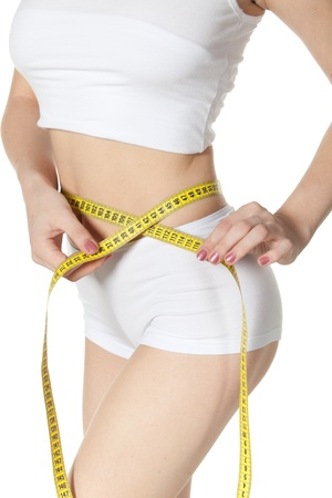 slim tummy: The beautiful girl measures a waist on a white background.  Healthy lifestyles concept.