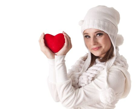 The beautiful young woman holds in hands a red heart on a white background.