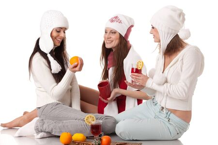 Beautiful young  women in winter clothes with mulled wine sit on a white background. photo