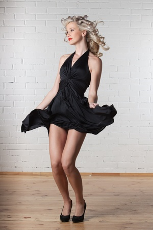 Young beautiful blond woman in black dress is dancing. photo