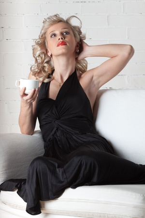 Attractive young woman lying on a white sofa with cup of coffee. photo
