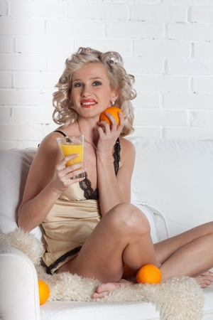 Young beautiful woman with  oranges and juice sits on a white sofa.  Concept  of healthy food. photo