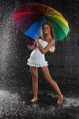 Young pretty woman with multi-coloured umbrella under rain on a black background. Stock Photo - 8732344