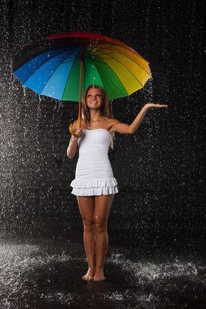 Young pretty woman with multi-coloured umbrella under rain on a black background. Stock Photo - 8725956