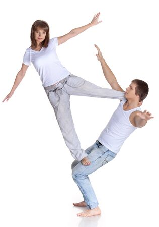 Young sports people carry out acrobatic tricks on a white background. Concept of teamwork. photo