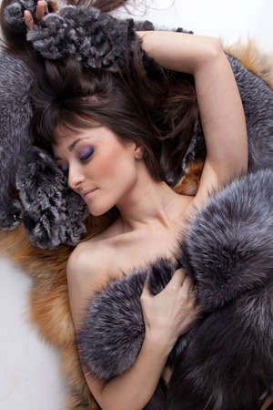 Portrait of young woman lying on furs on a white background. photo