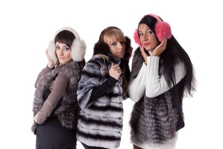 Three cheerful girlfriend in furs on a white background. photo
