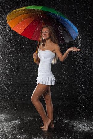 lluvia paraguas: Mujer joven y bonita con paraguas multicolor bajo lluvia sobre un fondo negro.