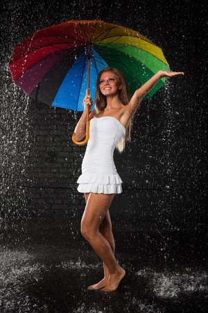 Young pretty woman with multi-coloured umbrella under rain on a black background. Stock Photo - 8806661