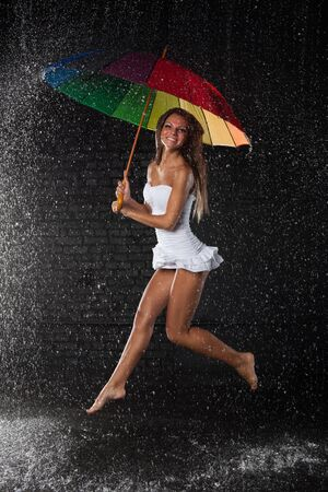 Young pretty woman with multi-coloured umbrella under rain on a black background. Stock Photo - 8806665