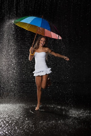 Young pretty woman with multi-coloured umbrella under rain on a black background. photo