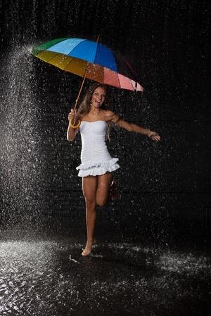 Young pretty woman with multi-coloured umbrella under rain on a black background. photo