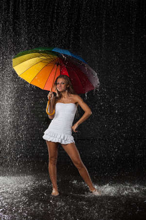Young pretty woman with multi-coloured umbrella under rain on a black background. Stock Photo - 8806664