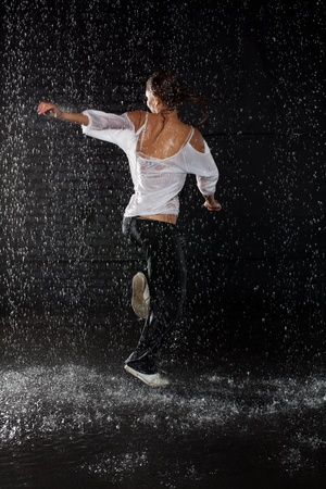 The beautiful girl dancing in water under rain on a black background.  Modern dances. photo