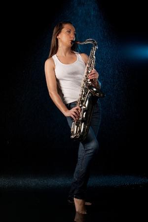 pantalones vaqueros mojados: Joven mujer hermosa con un saxof�n permanece bajo lluvia sobre un fondo negro. Foto de archivo