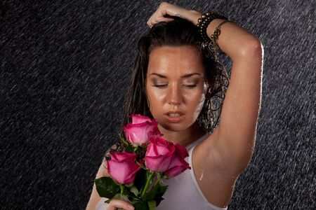 Young beautiful woman with roses stands under rain on a black background. photo