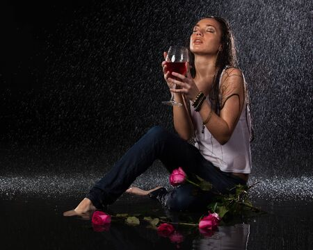 Young beautiful woman with roses and glass of wine sits under rain on a black background.
