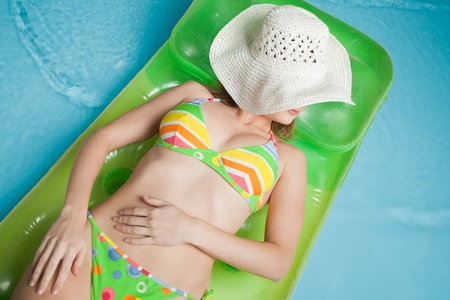 Beautiful young woman lies  on an inflatable mattress in the pool. Vacation. photo