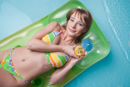 Beautiful young woman with fruit salad  lies  on an inflatable mattress in the pool. Vacation. photo