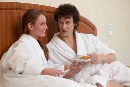 Happy young family  with breakfast lies in the bed at home. Stock Photo - 8806707