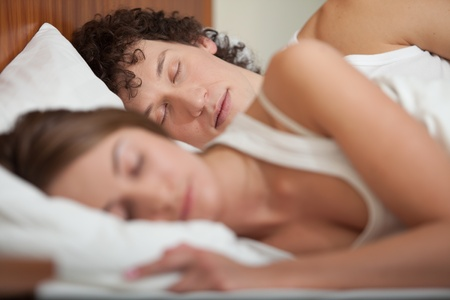 quietude: Happy young family sleep in the bed at home.  Selective focus on men.