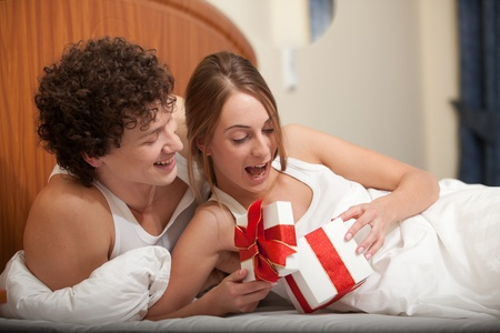 Happy young family with gift box lies in the bed at home. Valentines Day photo