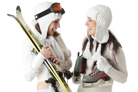 Beautiful young women in winter clothes with skates and skis  on a white background. Winter sports. photo
