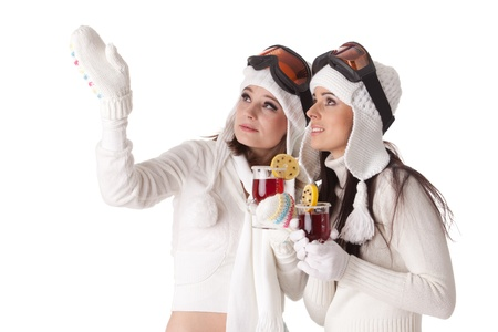 Beautiful young women in winter clothes and ski glasses drink mulled wine on a white background. photo