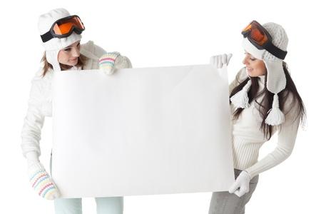 ropa de invierno: J�venes bonitas a mujeres en gafas de esqu� y ropa de invierno con Junta vac�a para el texto sobre un fondo blanco.