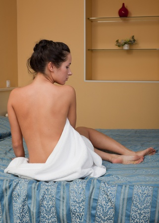 cosmetology: The attractive young woman in towel with cosmetic cream sits on bed at home. Concept of body care.