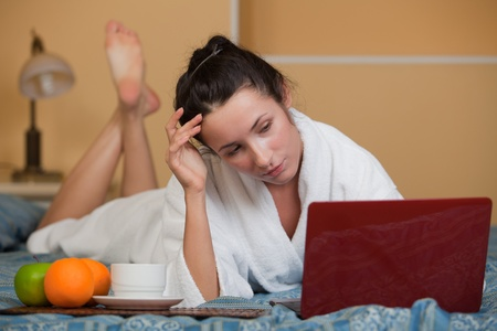 Young woman with laptop lies on the bed at home. photo