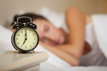 snoozing: Young sleeping woman and alarm clock in bedroom at home.