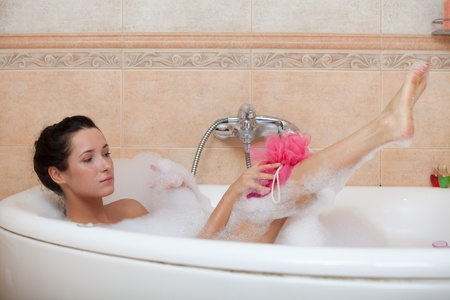 lying in bathtub: Portrait of a beautiful young woman in a bathroom. Concept body care.