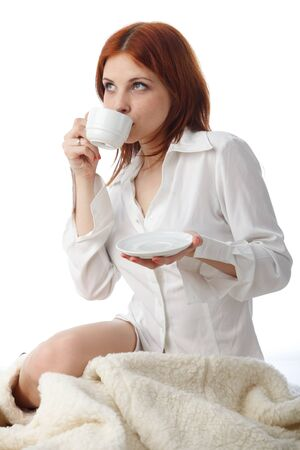 Young woman with  cup of coffee sits on warm plaid on a white background.