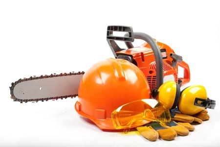 caja fuerte: Chain saw, cascos, orejeras, gafas protectoras y guantes sobre un fondo blanco