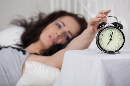 Young sleeping woman and alarm clock in bedroom at home. photo