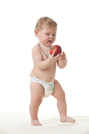 Sweet small baby with a fresh red apple on a white background.