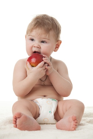 Sweet small baby with a fresh red apple on a white background. photo